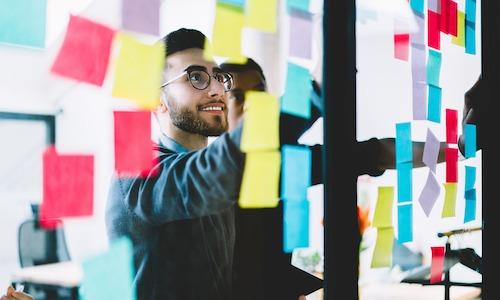 man looking at post it notes smiling